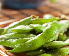 Cooked Green Organic Edamame with sea salt against a background